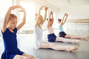 Ballet dancing children with hands up sitting in class