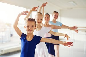 Young ballerinas dancing and looking at camera in class