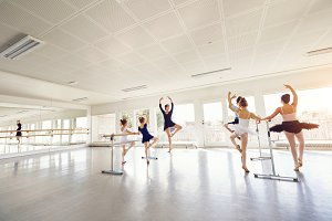 Woman showing ballet dance to children in class