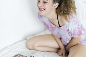 Girl smiling sitting on her bed.