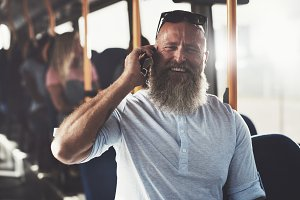 Laughing man standing in a bus talking on the phone