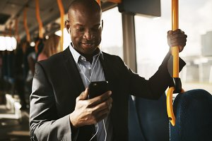 Young African businessman riding on a bus listening to music