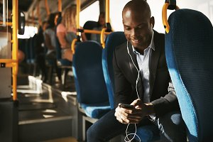 Smiling African businessman sitting on a bus listening to music