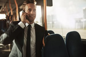 Smiling businessman talking on his cellphone during his morning commute