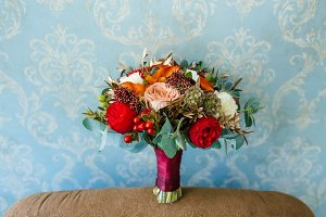 Flower arrangement for a wedding party. The bouquet of pink roses, red peonies, and other flowers on blue wall background. Wedding. Artwork