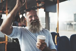 Smiling mature man with a beard and coffee on the bus