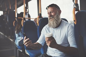 Mature man laughing at a text while riding the bus