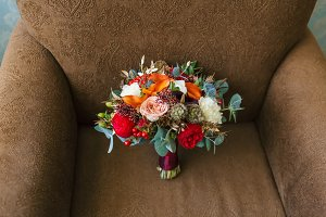Flower arrangement for a wedding party. The bouquet of pink roses, red peonies and other flowers on brown armchair. Wedding. Artwork. Soft focus
