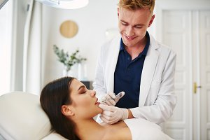 Doctor injecting botox into the lip of a female client