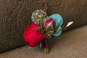 Groom's boutonniere with a red peony on a brown background. Wedding concept