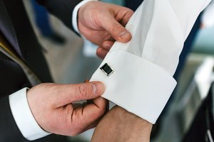 Groom's friend helps fasten cufflinks on groom's sleeve