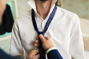 Groom's friend helps to fix a blue tie on groom's neck while they stand in the room
