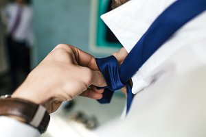 An unrecognizable groom in a shirt is tying a tie. Groom's accessories