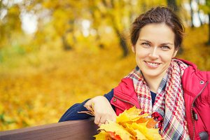 Portrait of young beautiful woman in autumn park