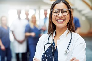 Smiling young doctor wearing glasses in clinic