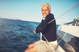 Mature man sitting on his sailboat looking at the ocean