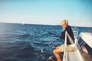 Mature man enjoying the ocean view from his sailboat