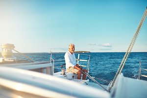 Smiling mature man sitting on the deck of his sailboat