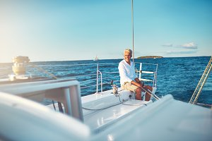 Mature man sitting on his boat out at sea