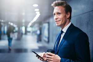 Smiling businessman waiting for a subway train reading text messages