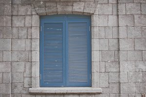 stony house wall with blue window