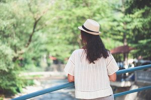 Rear view of brunette girl in park in brown hat
