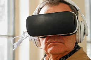 Senior old man wearing VR headset