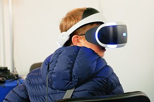 Child in VR headset playing digital virtual game