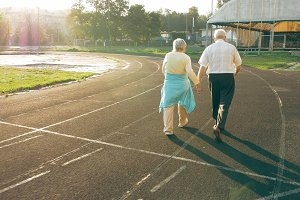 Senior couple walking along the running track