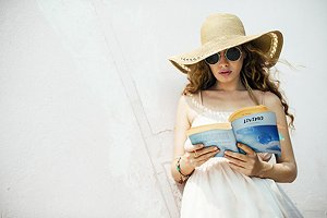 Woman with hat reading a book