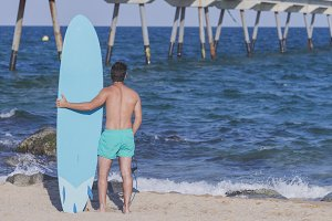 Surfer holding his surfboard