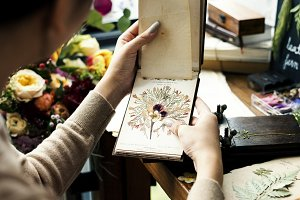 Hands holding dried flower book