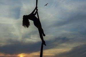 Woman aerial acrobat dances in the air.