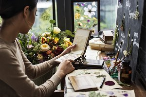 Woman looking a dried flower book