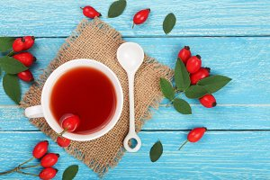 tea with rose hips on blue wooden background. Top view