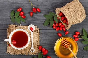 tea with rose hips on black wooden background. Top view