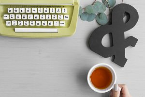 Typewriter with Hand Holding Tea Cup