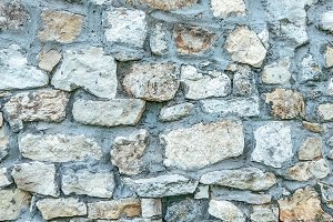 Stone old wall from huge blocks. Background of stones. The concept of reliability. The space between stones is filled with&#x2