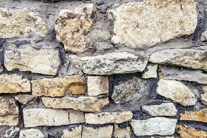 Stone old wall from huge blocks. Background of stones. The concept of reliability. The space between stones filled with cement.
