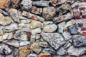 Stone old wall from huge blocks. Background of stones. The concept reliability. The space between the stones is filled with cement. Beautiful textured vintage antique background.