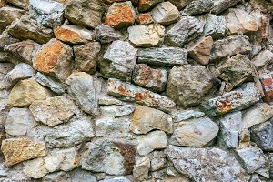 Stone old wall from huge blocks. Background of stones. The concept of reliability. The space between the stones is filled with cement.