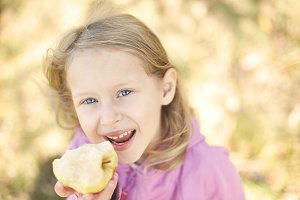 girl smiling and eating apple in the autumn on the nature walk outdoors