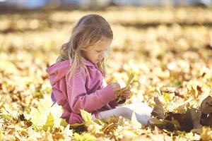 girl laughing and playing in the autumn on the nature walk outdoors