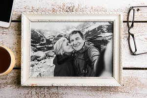 Black-and-white photo of senior couple in white picture frame.