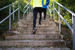 Unrecognizable athletes running on stairs on sunny autumn day.