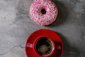 Pink glazed donut with coffee
