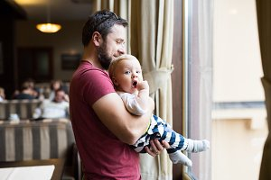 Handsome young man in cafe with his cute baby son