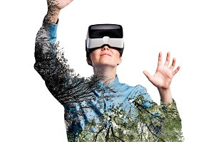 Double exposure. Woman with virtual reality goggles. Trees.