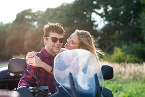 Couple in love enjoying a motorbike ride in countryside.
