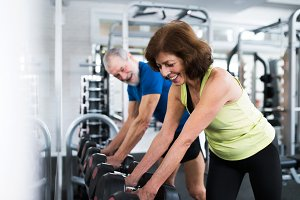 Senior couple in gym working out with weights